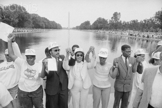 Washington DC. Mrs. Coretta Scott King, widow of Martin Luther King, Jr., joins hands with others at the reflecting pool near the Lincoln Memorial in the hands across America celebration 5/25. the Washington Monument is in the background.  © Bettmann/CORBIS